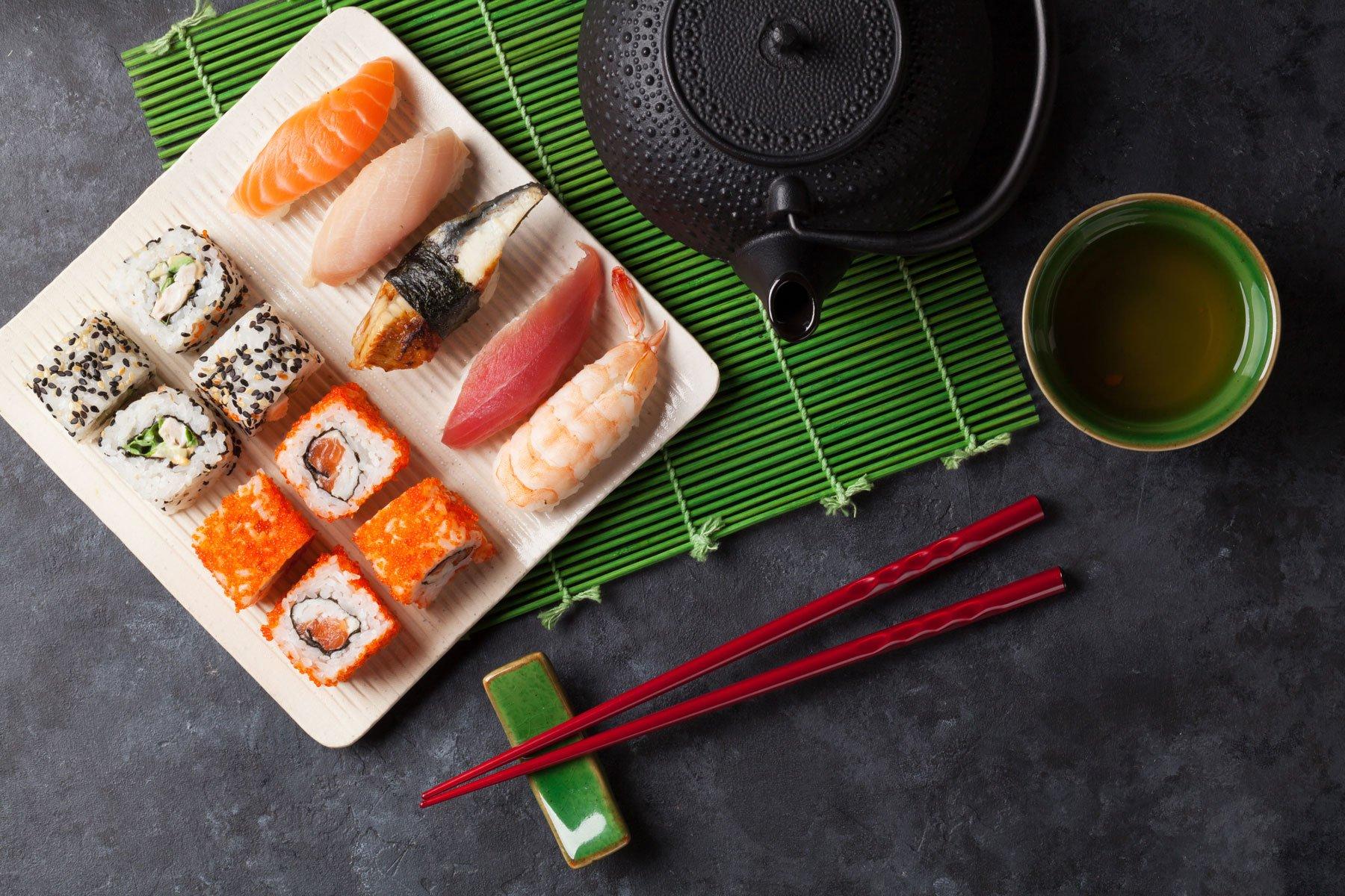 un piatto di sushi, delle bacchette rosse una ciotola di tè verde e ujna teiera, il tutto su una tovaglietta verde di bambù