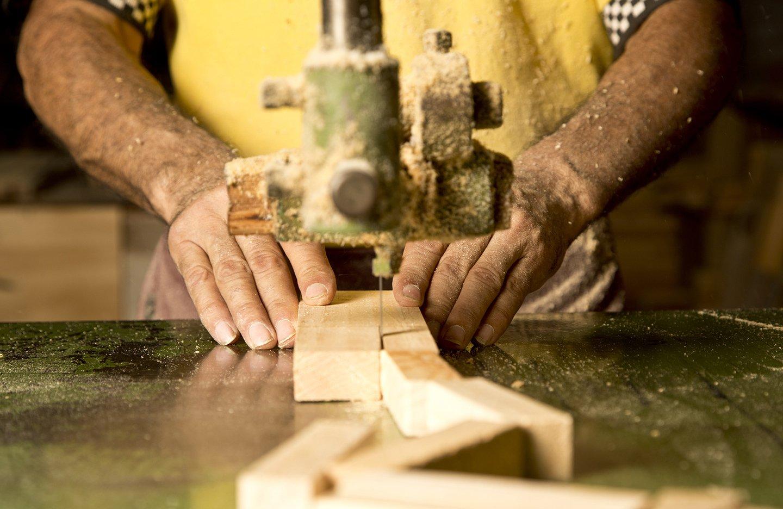 falegname mentre taglia un pezzo di legno con una macchina