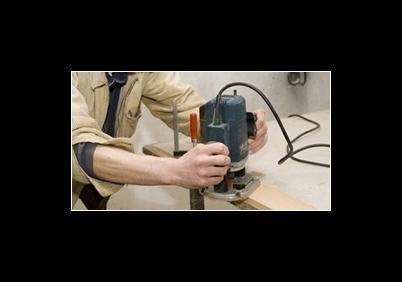 operaio mentre taglia il legno con una macchina