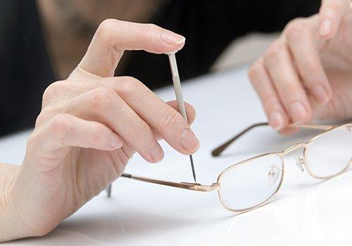 due mani mentre stringono vite degli occhiali da vista dorati