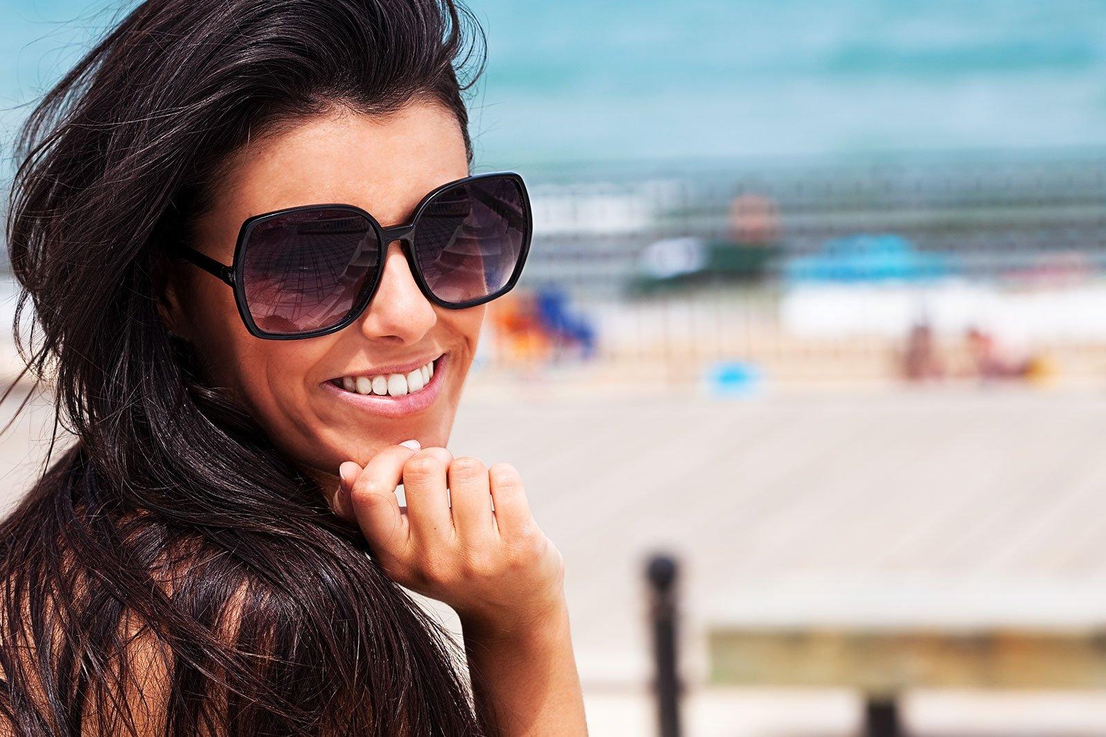 una ragazza con degli occhiali da sole neri e vista di una spiaggia
