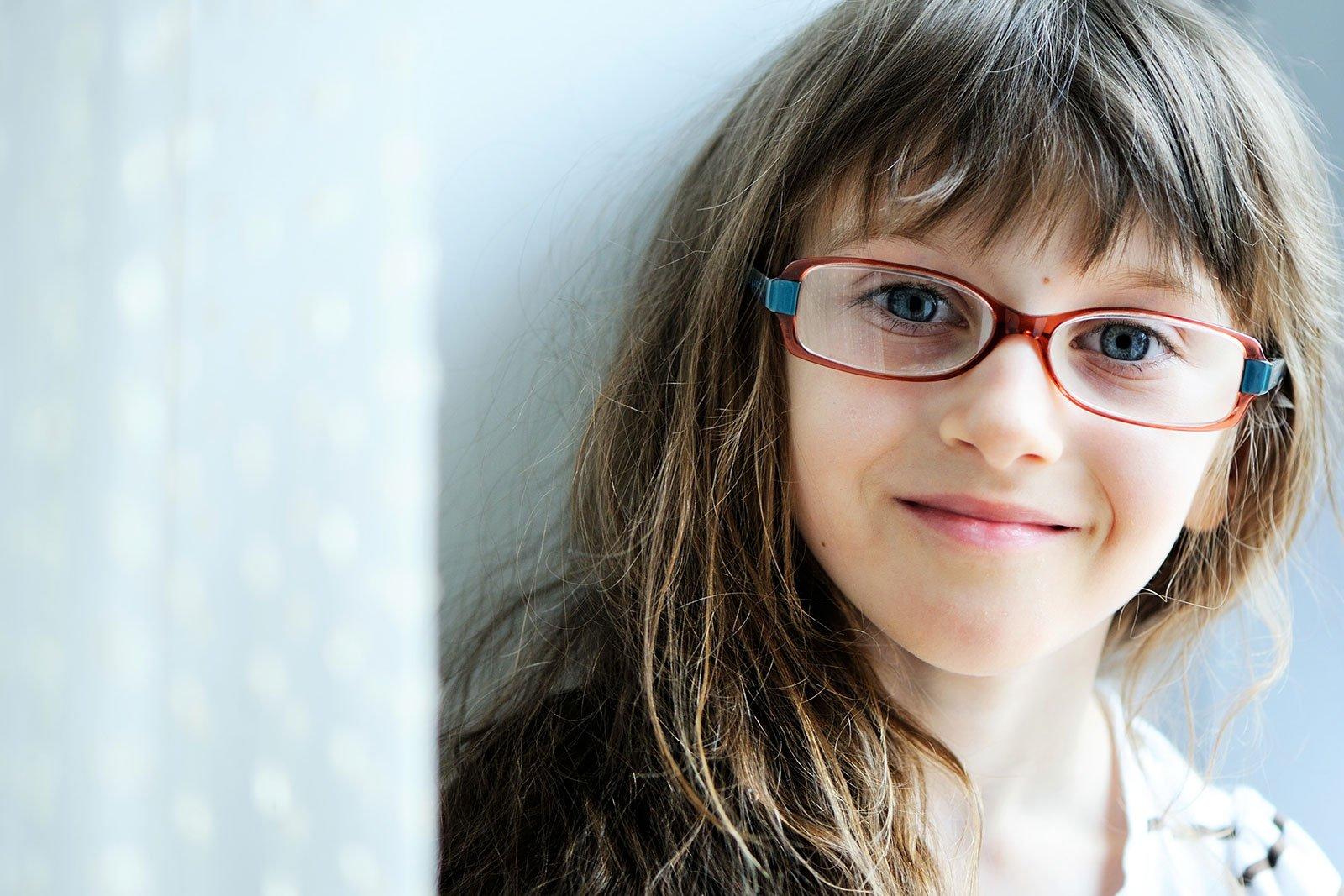 una bambina con degli occhiali da vista rossi