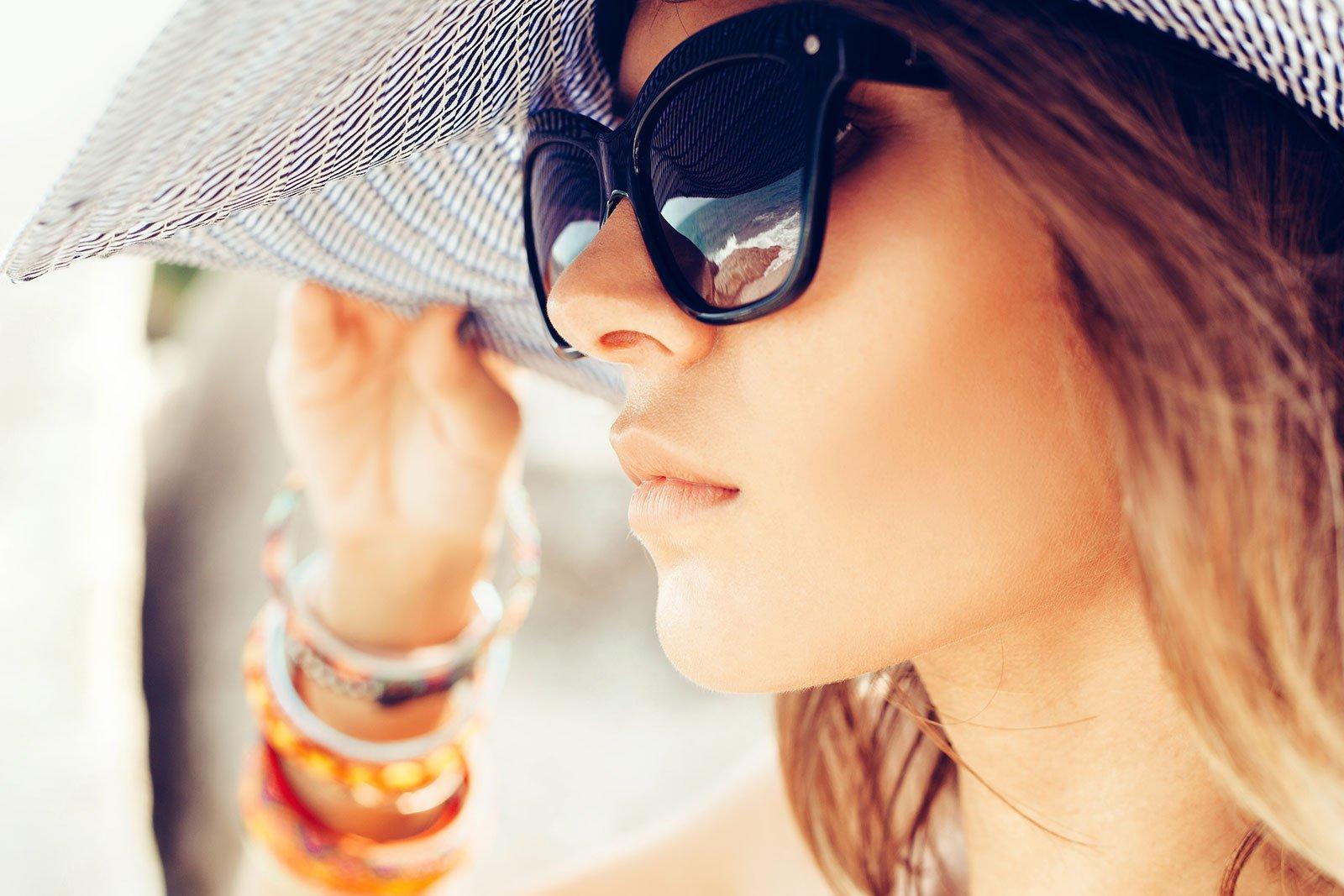una ragazza con un cappello e degli occhiali da sole neri vista di profilo