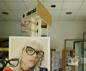 dei cartelli pubblicitari che sponsorizzano degli occhiali all'interno del negozio