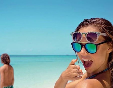 una ragazza con due paia di occhiali da sole e dietro vista del mare