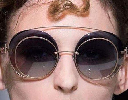 un primo piano di una ragazza con degli occhiali da sole