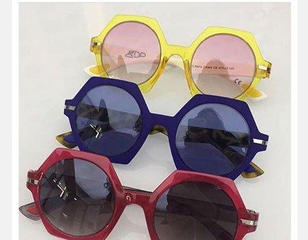 tre paia di occhiali da sole bordeaux, blu e gialli