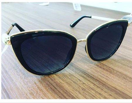 un paio di occhiali da sole, dei jeans e una maglietta bianca della marca Guess