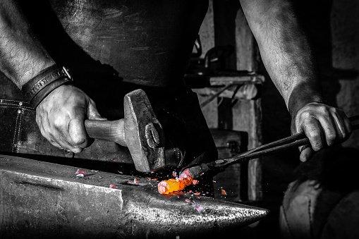 Fabbro martella un pezzo di ferro su un'incudine