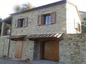 uno stabile di pietra con le porte in legno e due finestre aperte