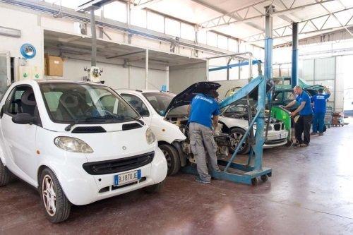 Tre meccanici che lavorano su un auto in riparazione