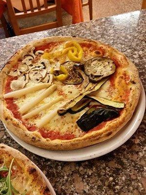 una pizza con funghi, peperoni e verdure grigliate