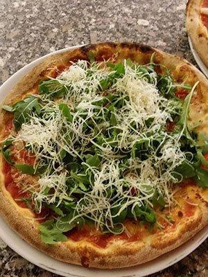 una pizza con sopra insalata e formaggio grattugiato