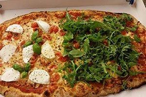 una pizza con rucola, pomodorini e mozzarella di bufala