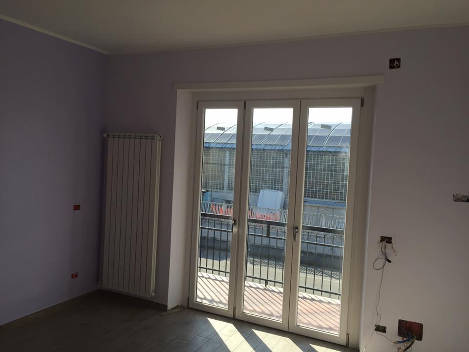una porta finestra in pvc bianco e accanto un termosifone