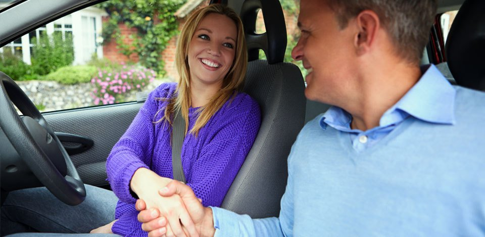 A young female driver shaking hands with her instructor