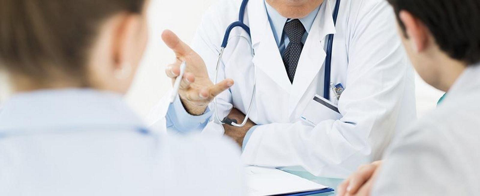 tre medici mentre parlano seduti al tavolo