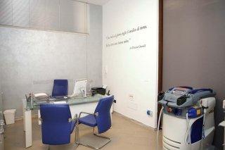 una scrivania con tre sedie e accanto un apparecchio medico