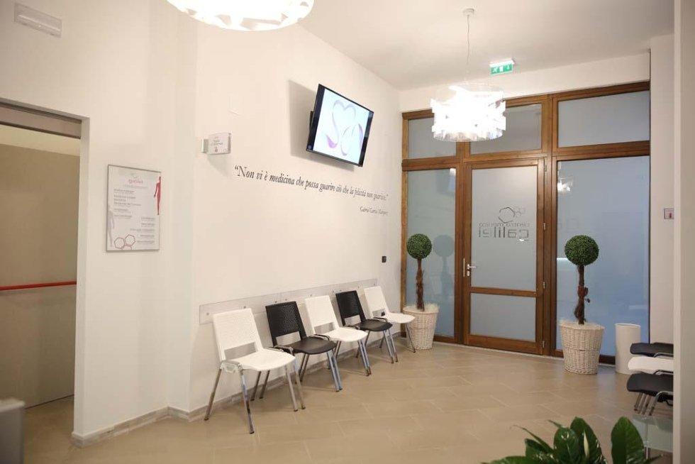 una sala di attesa con le sedie e un monitor al muro