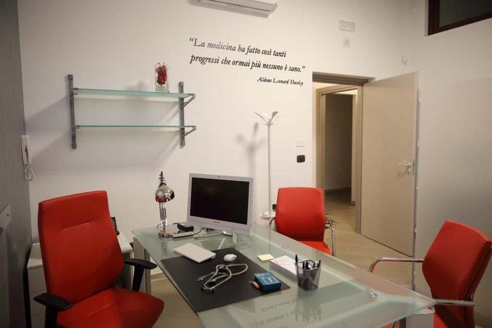 una scrivania in vetro con un monitor, uno stetoscopio e accanto delle sedie rosse