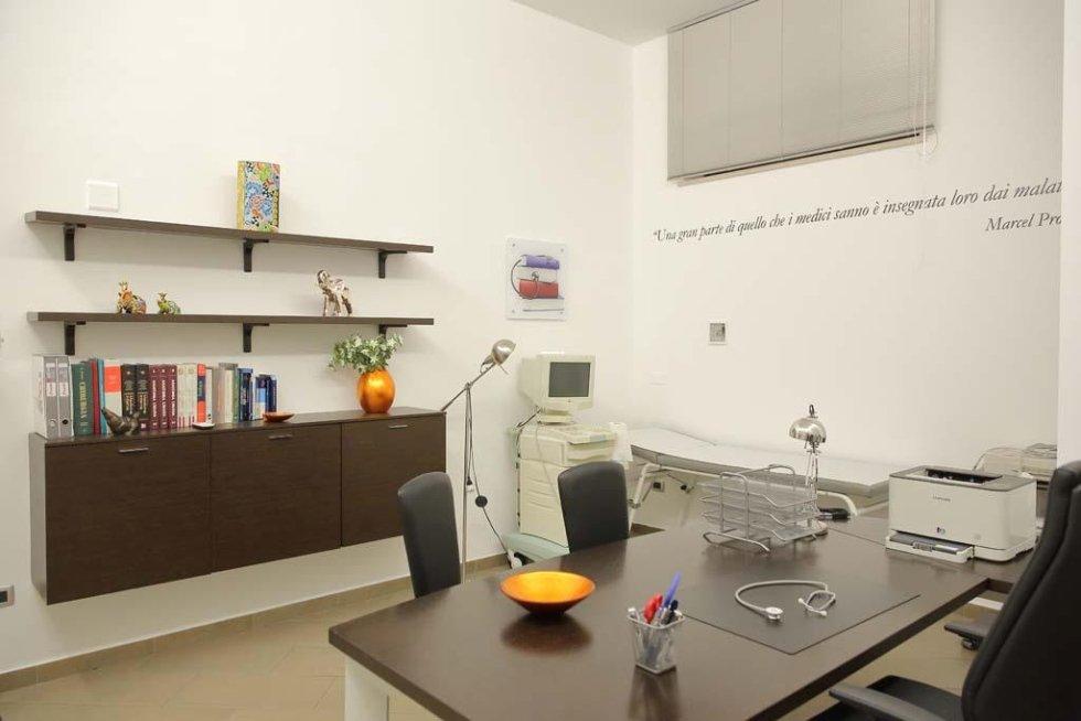 un ufficio con una scrivania, un mobile, delle mensole e un apparecchio elettromedicale