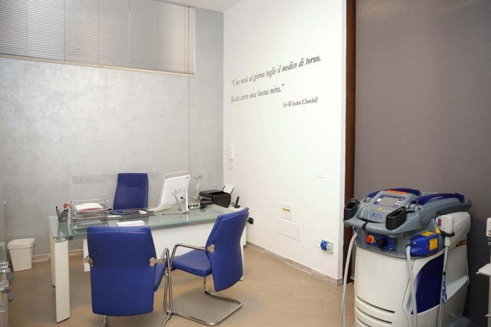 una scrivania in vetro con delle sedie blu e un apparecchio medico