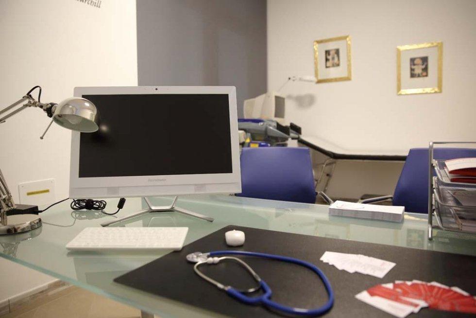 una scrivania con un  monitor, tastiera,mouse e uno stetoscopio