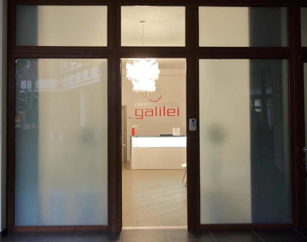 una reception e la scritta sul muro centro medico Galilei vista da una porta socchiusa