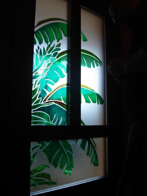 una vetrata con dei disegni delle foglie di una pianta