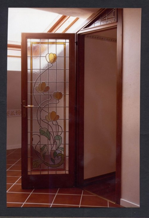 una porta in legno e vetro  con dei disegni a fiori colorati