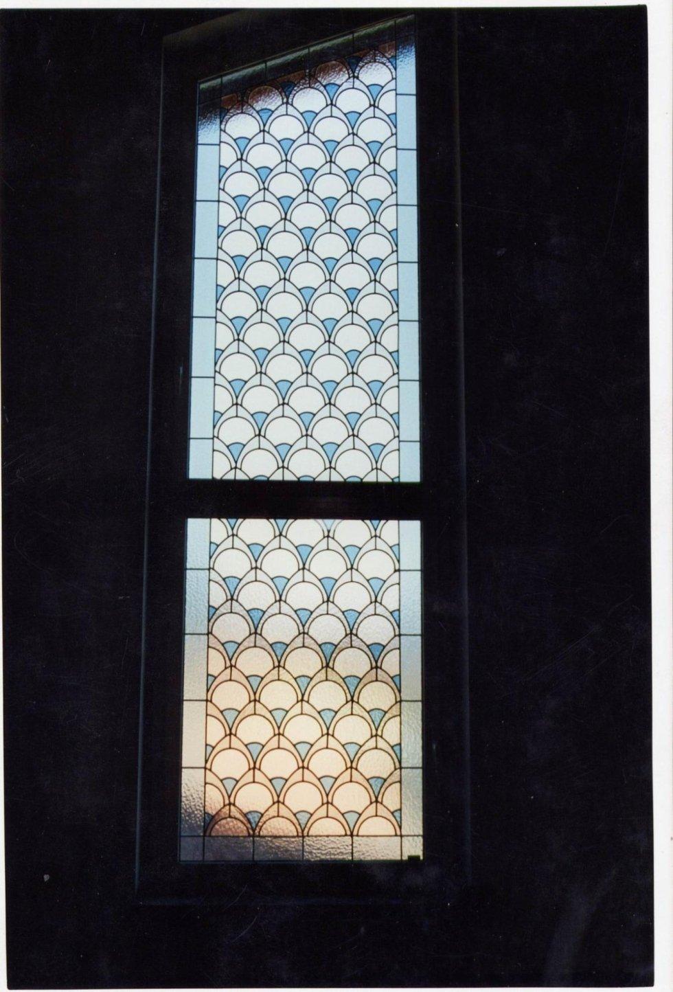 una vetrata con un disegno del mare e di un gabbiano