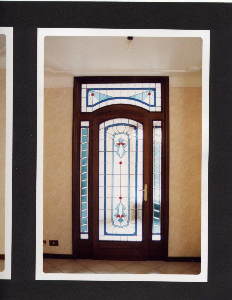una porta in vetro con disegni azzurri e rossi