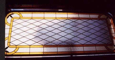 una vetrata rettangolare con disegni gialli a griglie nere