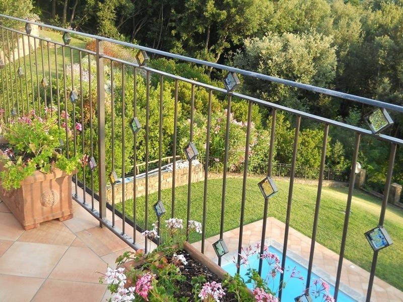 un balcone con una ringhiera e vista di una piscina nel giardino