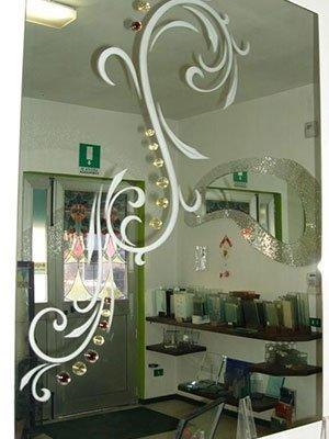 Specchio con arabesco bianco e decorazione di pietre rosse e gialle