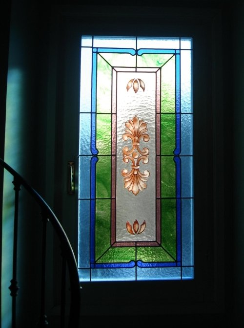 una vetrata blu, verde, rosa con dei gigli