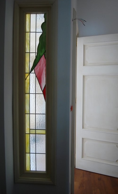 una vetrata gialla e bianco con un disegno verde e rosso