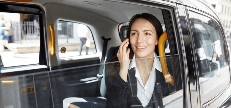 A lady in a black jacket and white shirt, sitting in the back of a taxi, talking on a mobile phone