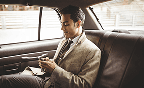 A man in a suit and tie, in the back of a taxi, reading his messages