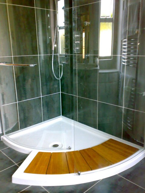 fitted curved wooden duckboard at shower entrance