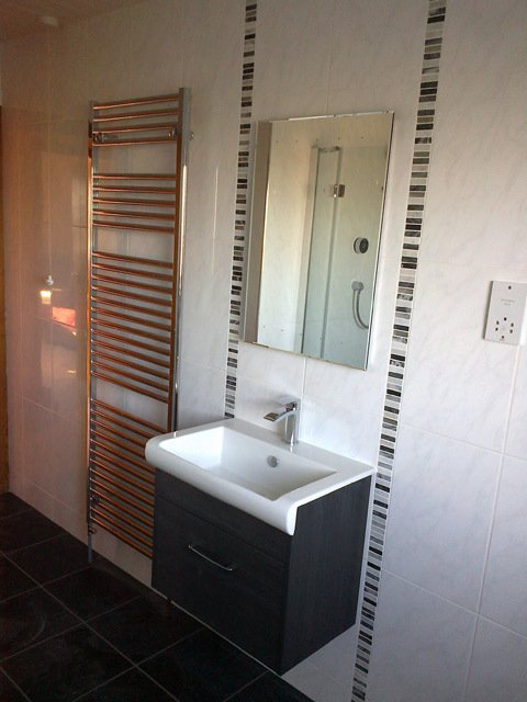 wall mounted handbasin and draawers with wall towel heater and designer tiling