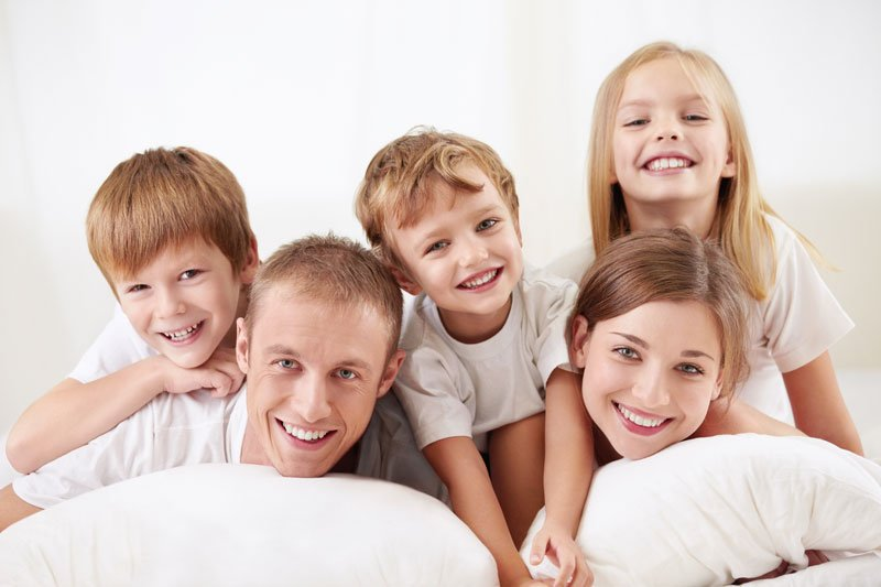 Happy family with children on bed in NY