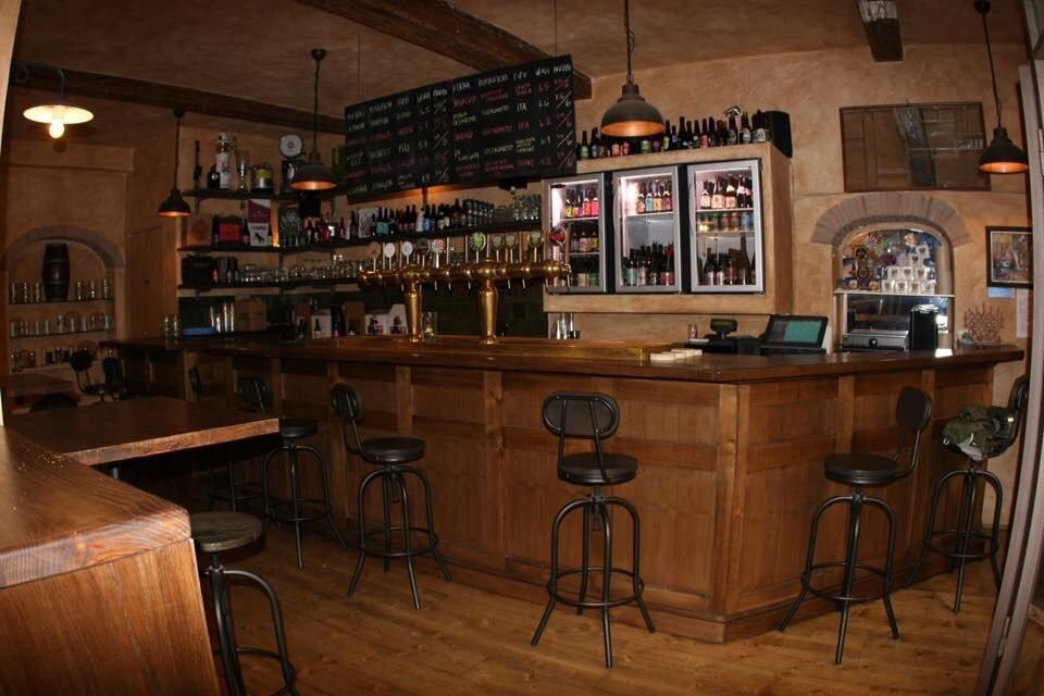 l'interno di una birreria con un bancone di legno e delle sedie