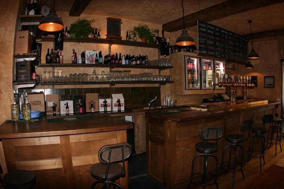 l'interno del locale con il bancone e delle sedie di legno