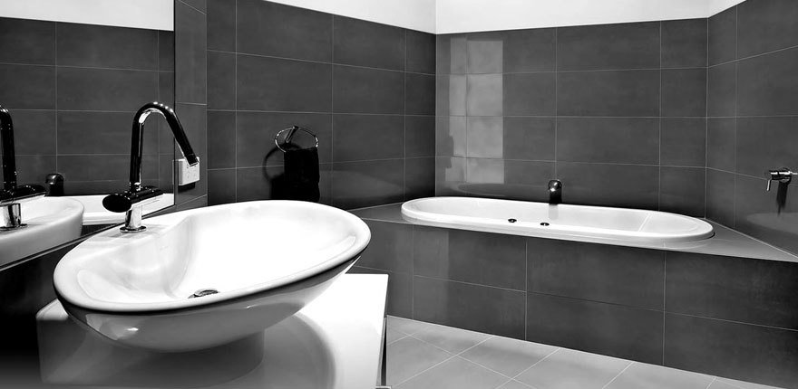 A white bath and washbasin in a graphite tiled bathroom
