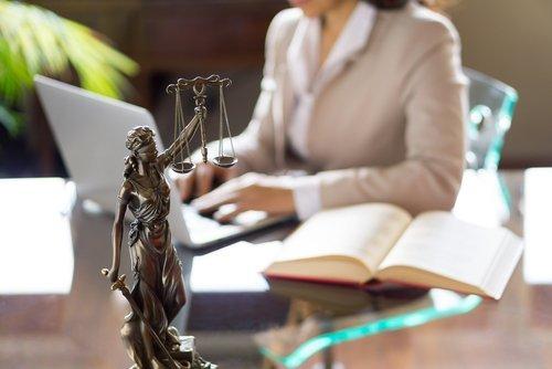 Donna avvocato che lavora al computer portatile e la statua della giustizia
