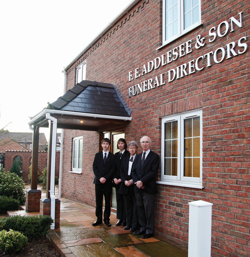 The funeral directors standing in front of the company building