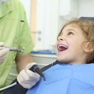 bambina sorridente durante la visita odontoiatrica