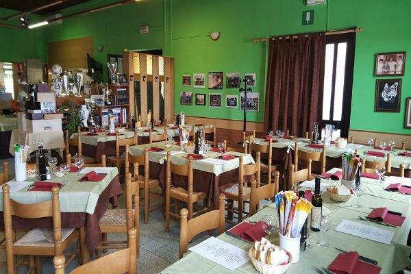 dei tavoli apparecchiati con tovaglie bianche e rosse