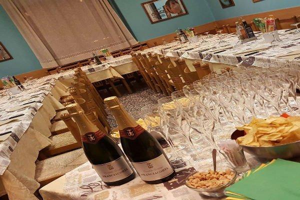 una lunga tavola apparecchiata con due bottiglie di champagne